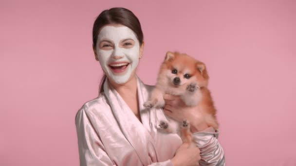30s brunette woman with her pet dog makes a facial mask routine