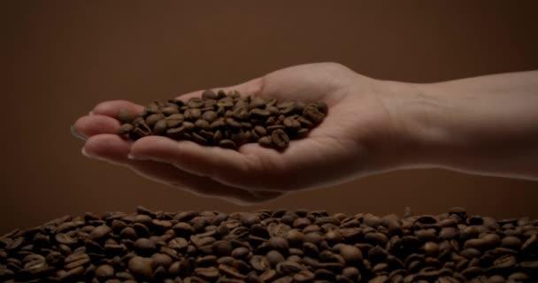 samičí ruka plná kávových zrn se otáčí a kávová zrna pomalu padají