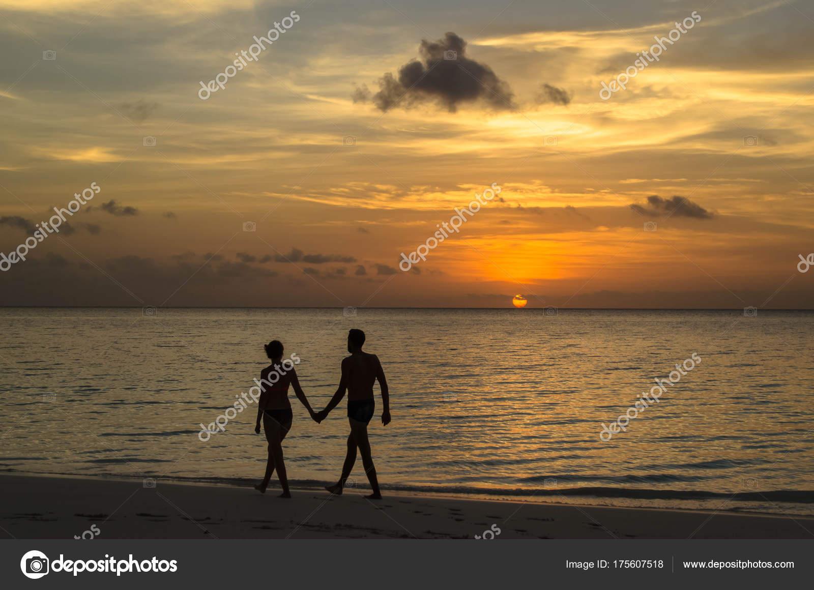 手を繋いでいる海岸に沿って歩く...