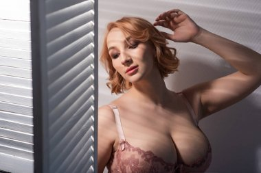A beautiful young woman with very large natural breasts is standing by the window with shutters. A girl in pink lace shows a beautiful figure next to a white screen. Huge female boobs.