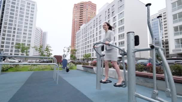 A woman in a business suit and heels engaged in the simulator is the outdoors playground . Business woman in glasses doing leg exercises during lunch break.