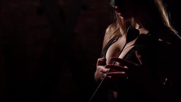 Nerozpoznatelná žena v krajkové černé spodní prádlo drží bič mezi krásnými velkými ňadry. dívka v kožené masce v roli milenky. Bdsm