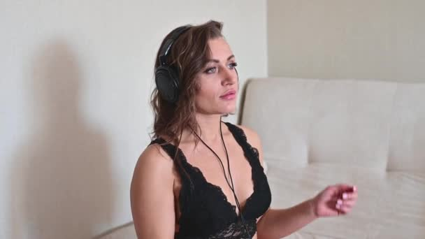Beautiful woman in black lace underwear enjoying listening to music. The girl in the bedroom takes off her headphones and looks confusedly at the camera.
