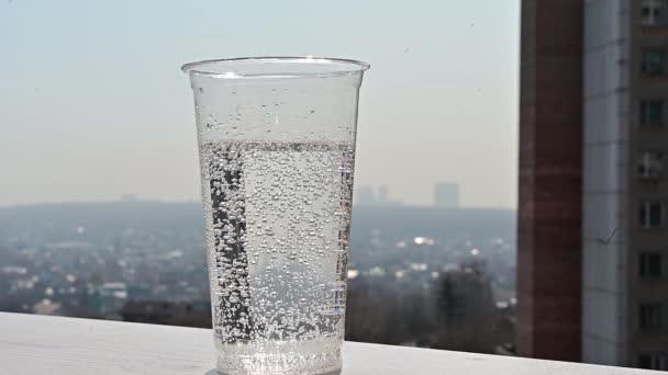 Zpomalené video plátek citronu padá do průhledné plastové sklenice se sodou. Osvěžující koktejl u okna s výhledem na město. Horký letní den.
