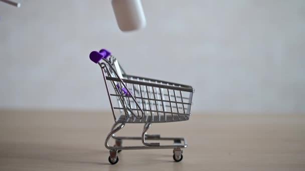 Lékárník v těsnění naplňuje mini nákupní košík různými léky na virovou respirační chorobu. Léky nosní sprej a tableta v vozíku. Léky v lékárně.