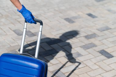 Closeup of a female hand in a glove on a luggage handle. A woman is walking down the street and with a big blue bag. Travel concept during a virus outbreak. Personal hygiene