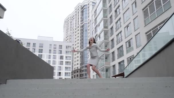 Successful business woman dancing and jumping for joy on the street. Beautiful girl in a business suit rejoices on the stairs. Slow motion.