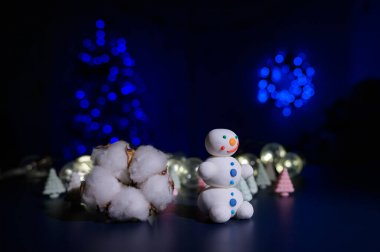 A sweet snowman from a pastry mastic on a background of marshmallow trees and a white mug with cocoa. Sweets and a bud of hlok in the dark against the background of a Christmas tree in the lights.