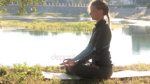 Frau sitzt mit geschlossenen Augen in Lotusposition auf dem Land.