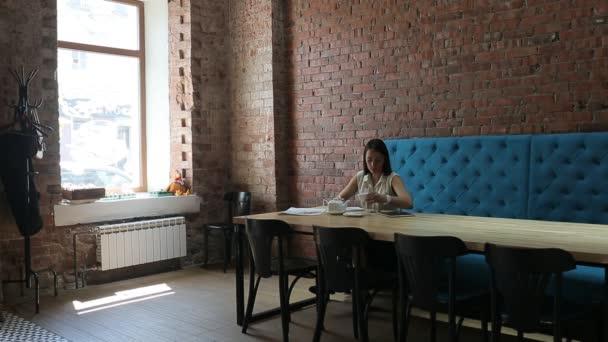 Atraktivní žena pije kávu a zápisy, posezení v restauraci