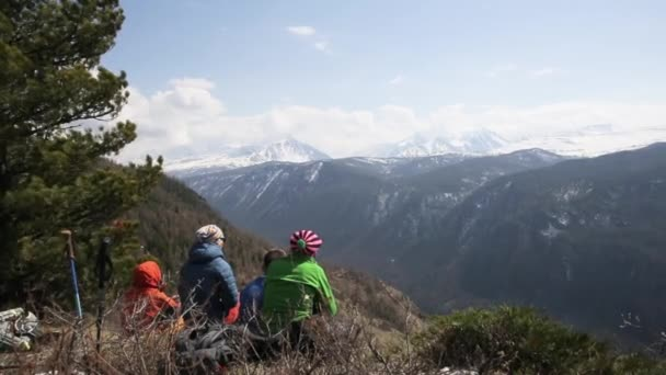 Skupina turistů se sedí na vrcholu kopce a pozorování montains s vrcholky sněhu