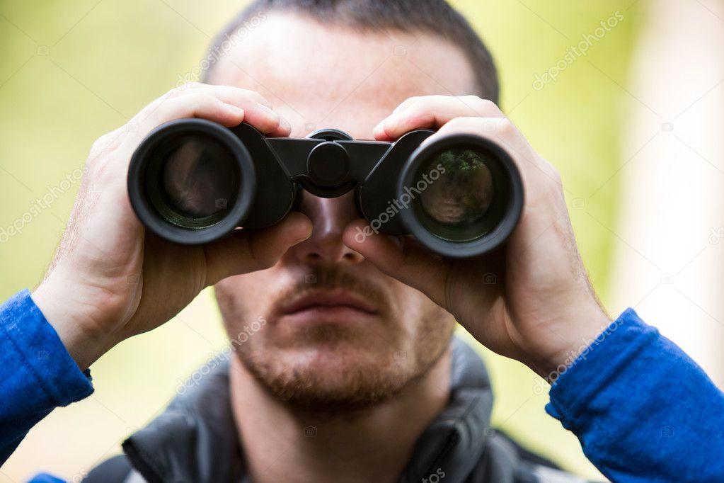 Männliche wanderer durch ein fernglas schauen u stockfoto