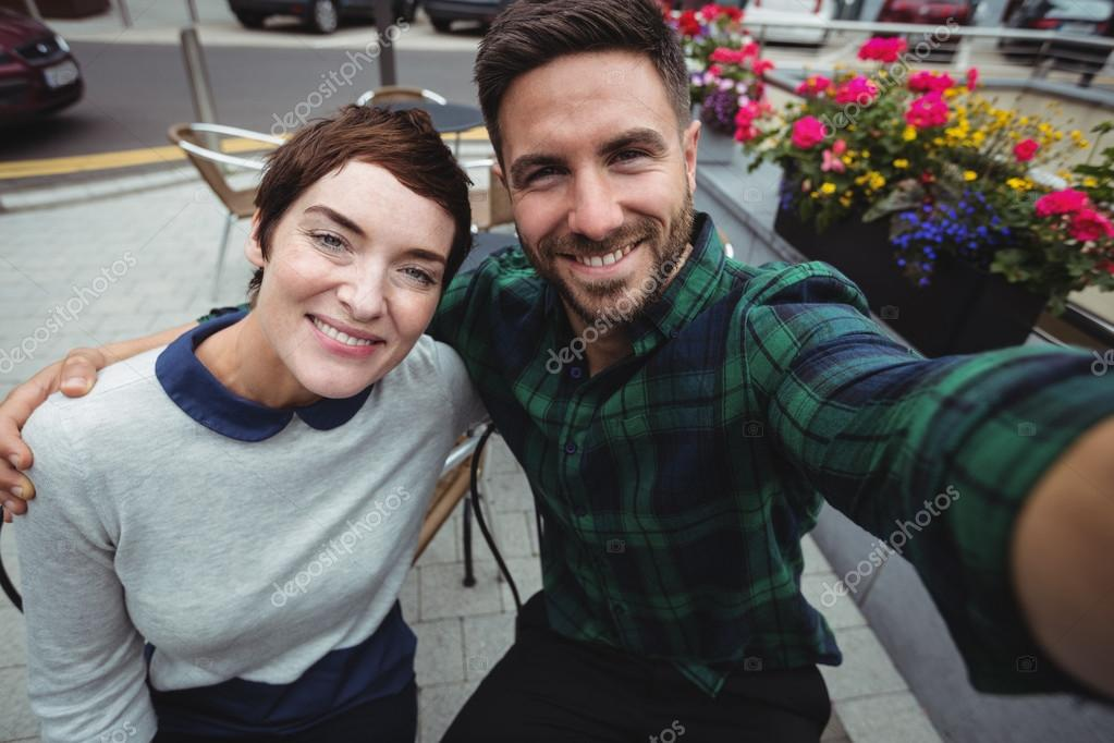 Couple Posing For Selfie In Cafeteria Stock Photo