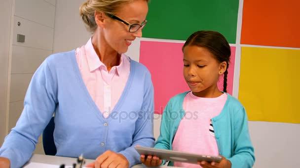 Schoolgirl And Teacher Using Digital Tablet Stock Video