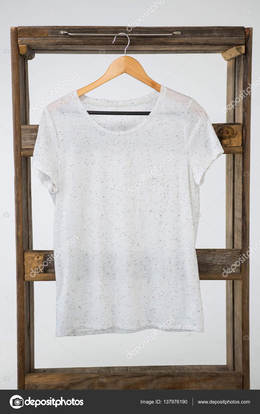 White t-shirt hanging on wooden frame — Stock Photo © Wavebreakmedia ...