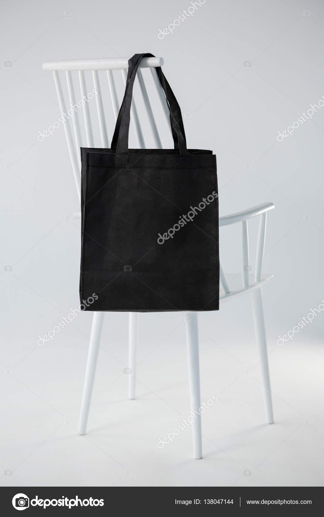 Sac Noir Accroche Sur Une Chaise Blanche Fond Blanc Image De Wavebreakmedia