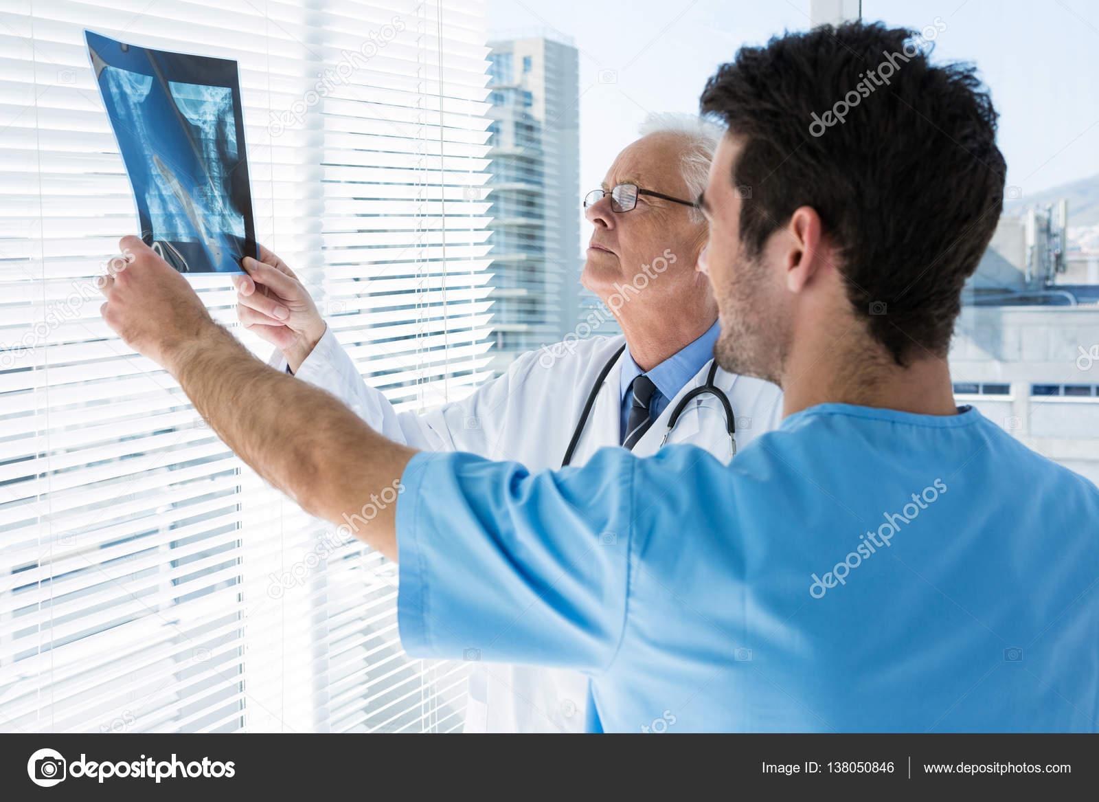 Chirurg und Arzt Röntgen-Bericht — Stockfoto © Wavebreakmedia #138050846