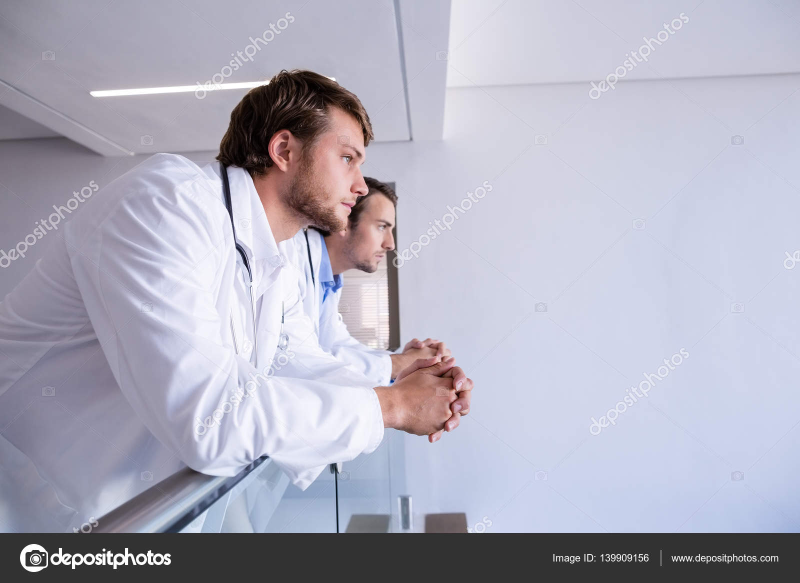 doctors leaning on railing in corridor stock photo