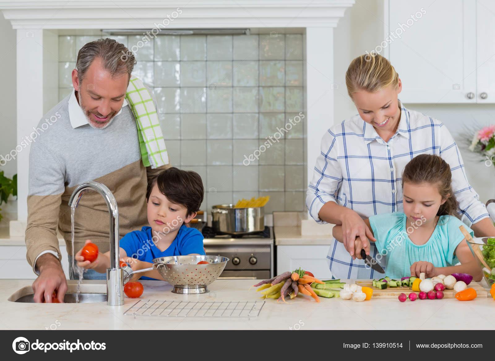 Padres ayudando a los ni os para picar y limpiar las for Cocina en familia