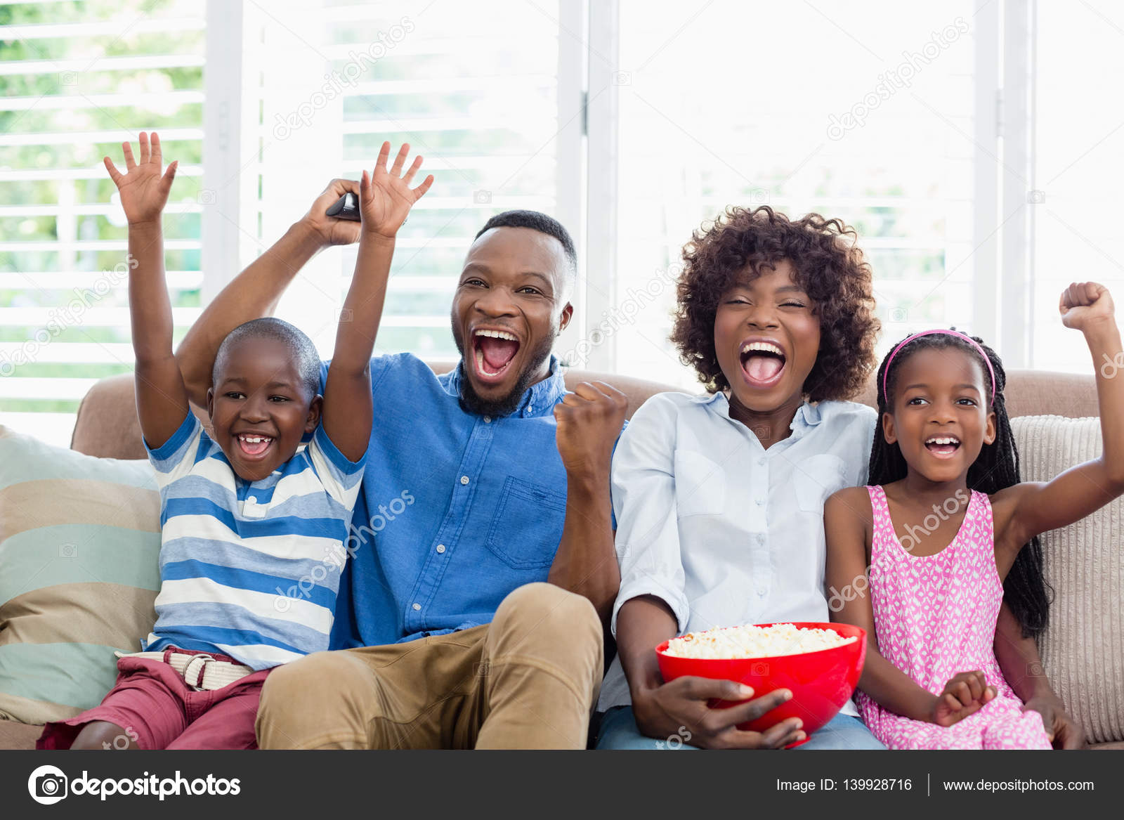 Excited family and kids watching television while having ...