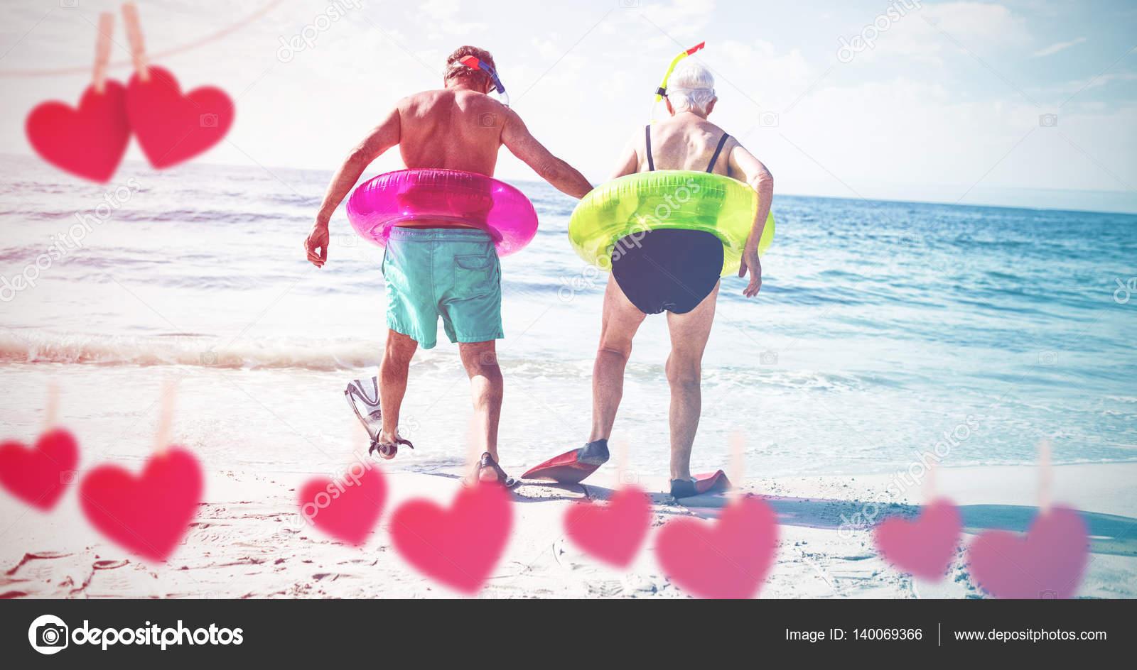 Pareja en anillo inflable y aleta caminando en la playa: fot