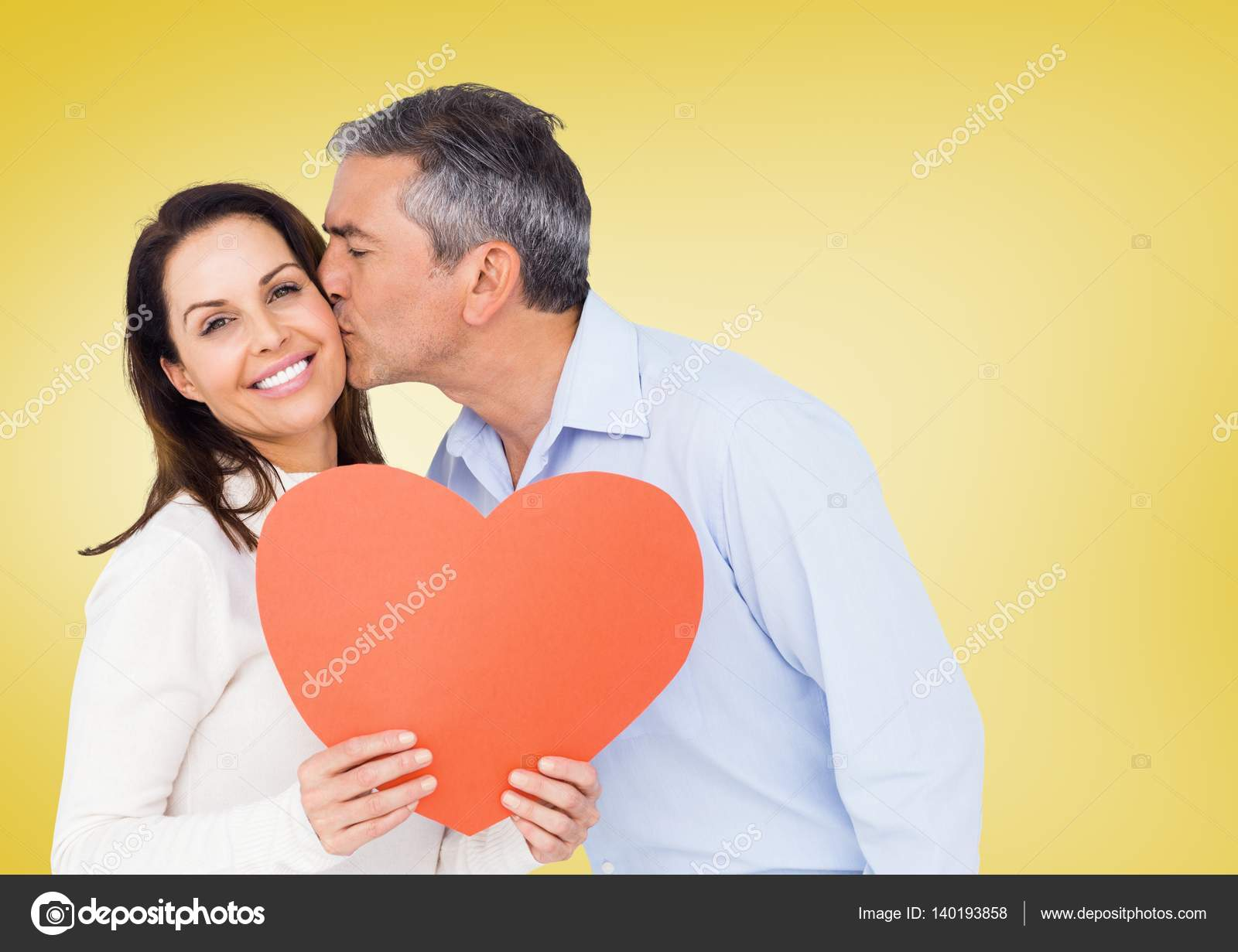 mature man kissing woman holding red heart — stock photo
