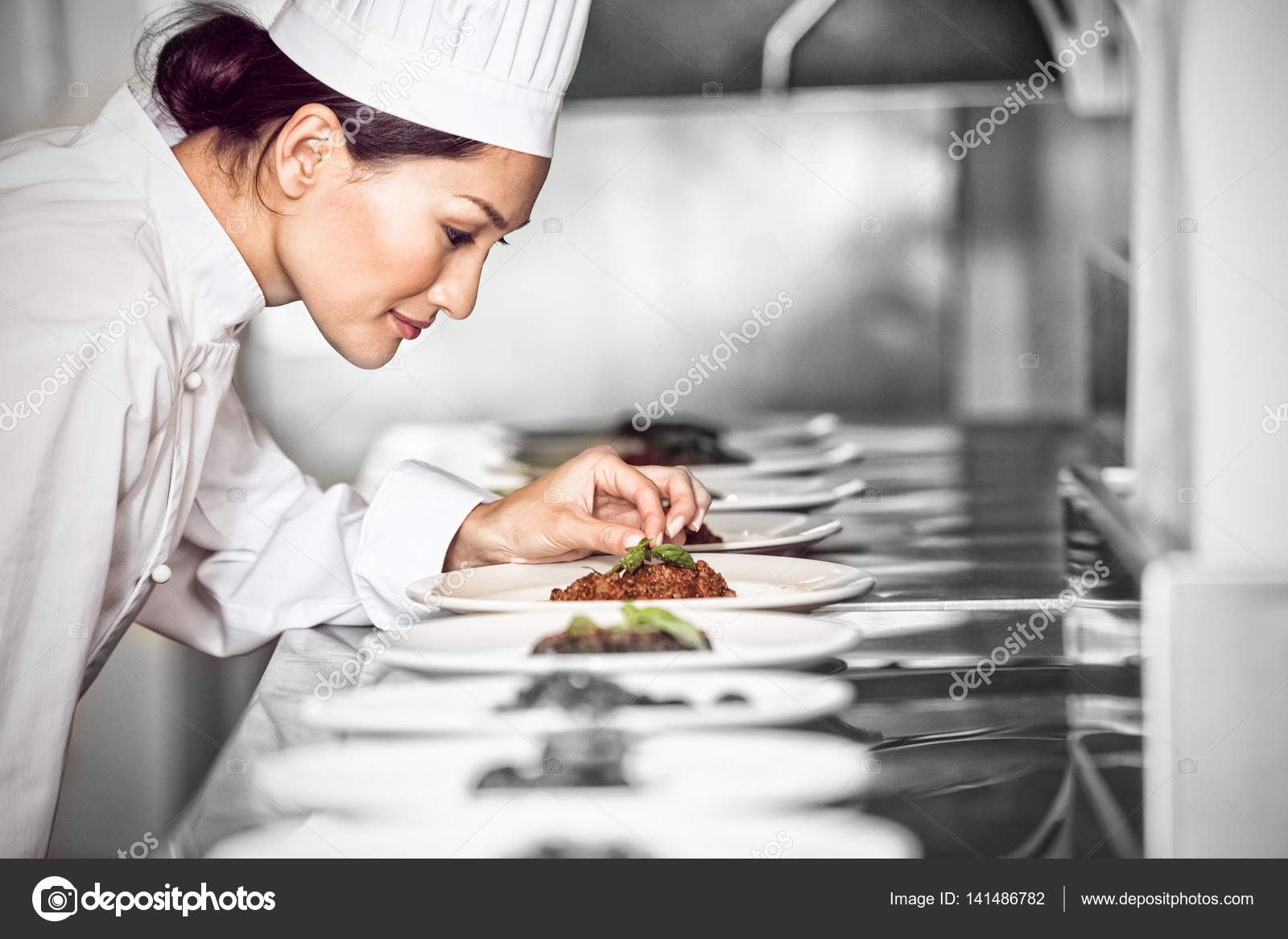 Concentrated female chef garnishing food in kitchen — Stock Photo ...