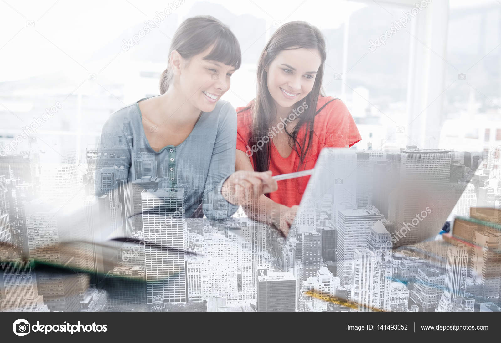Two Girls Smiling As They Use The Laptop One Girl Points At Something Stock