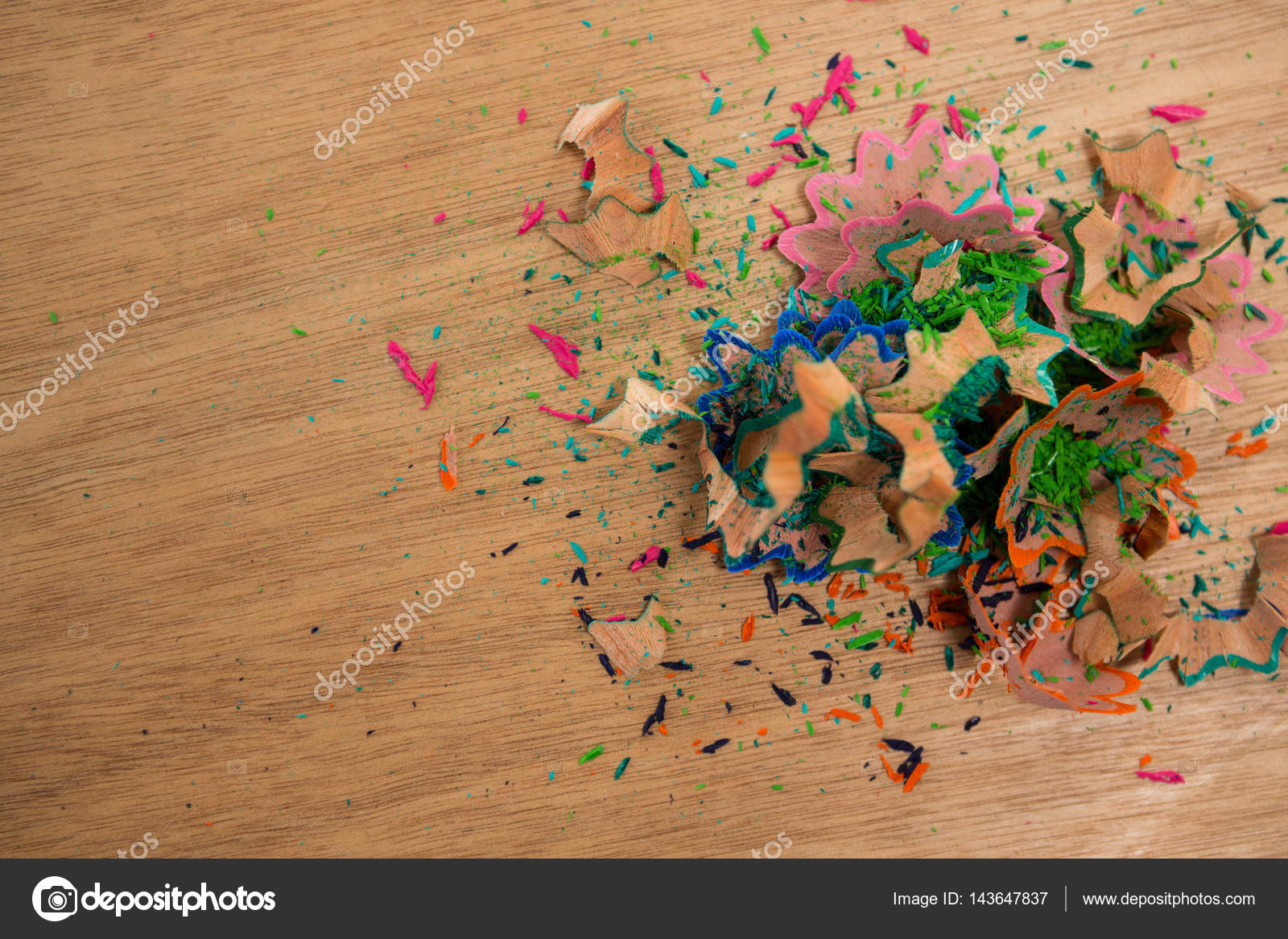 Colored pencil shavings on wooden background — Stock Photo
