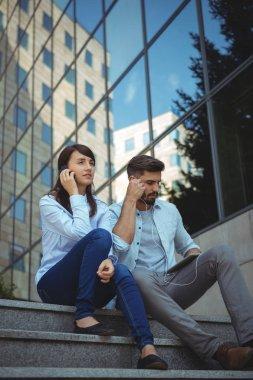 Executives listening music on digital tablet
