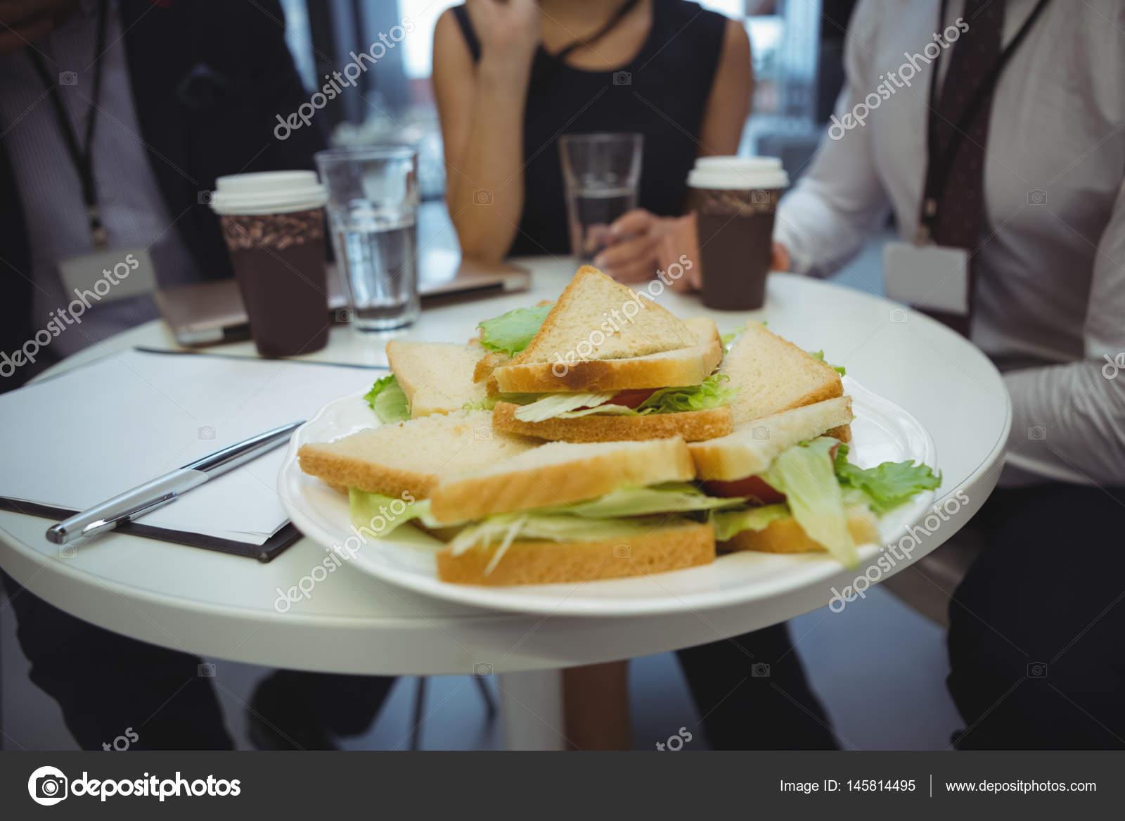 Primer plano de desayuno en la mesa con gente de negocios for Mesa desayuno