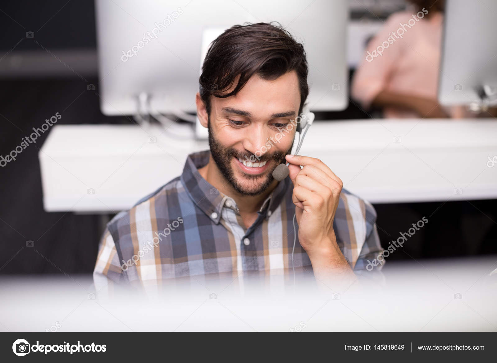 Smiling Male Customer Service Executive Talking On Headset