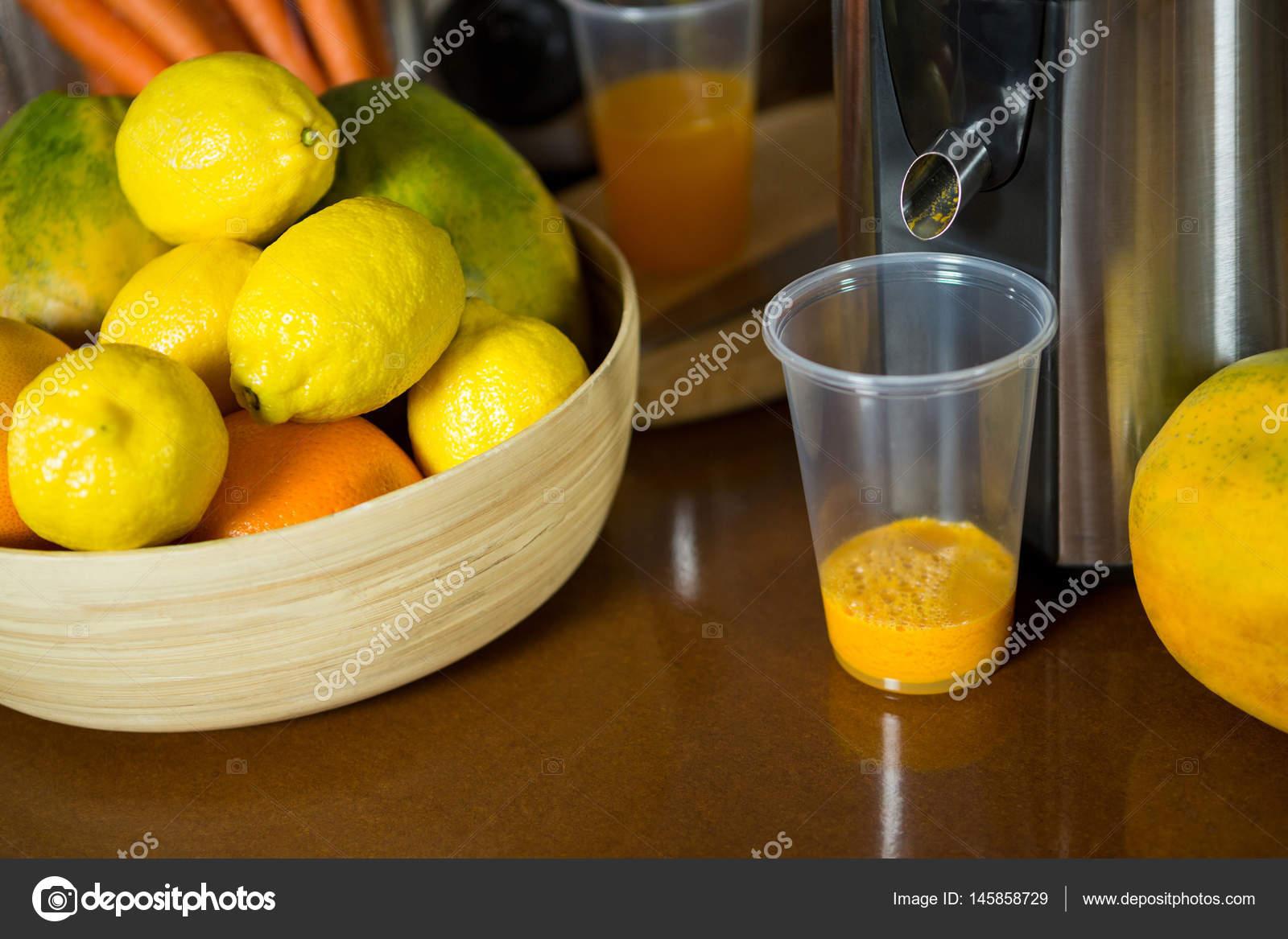 Limones en Bol de madera con vaso de jugo en el contador de — Fotos ...
