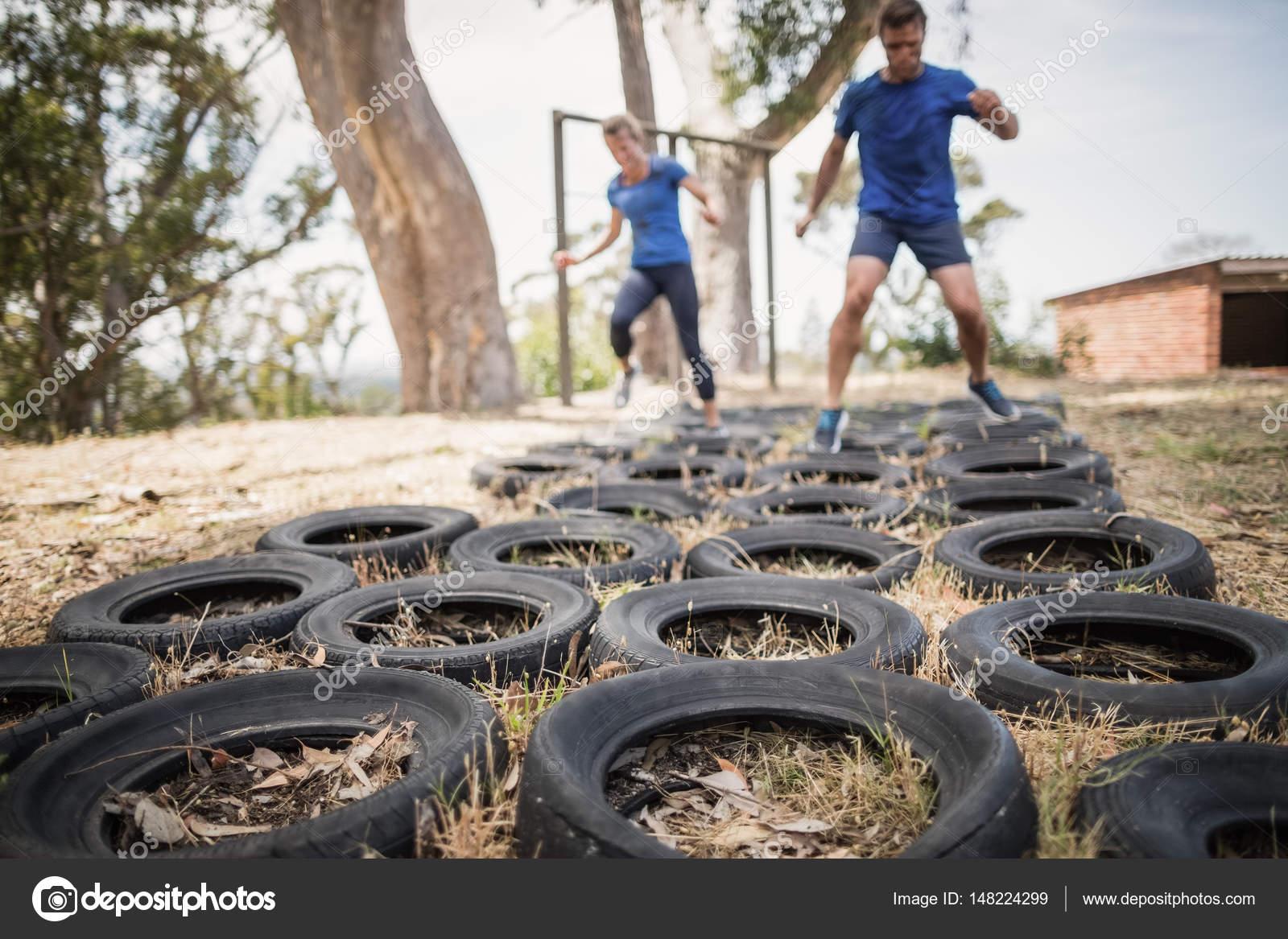 Klettergerüst Reifen : Mann und frau läuft über den reifen u2014 stockfoto © wavebreakmedia