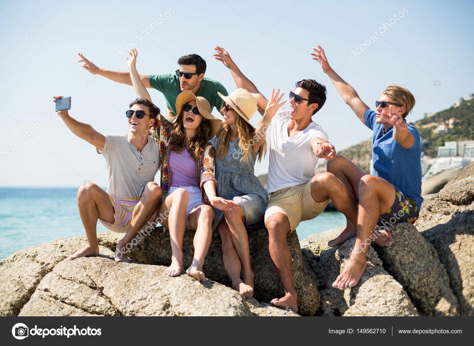 meisje, zittend op een rots door de zee en het spelen van