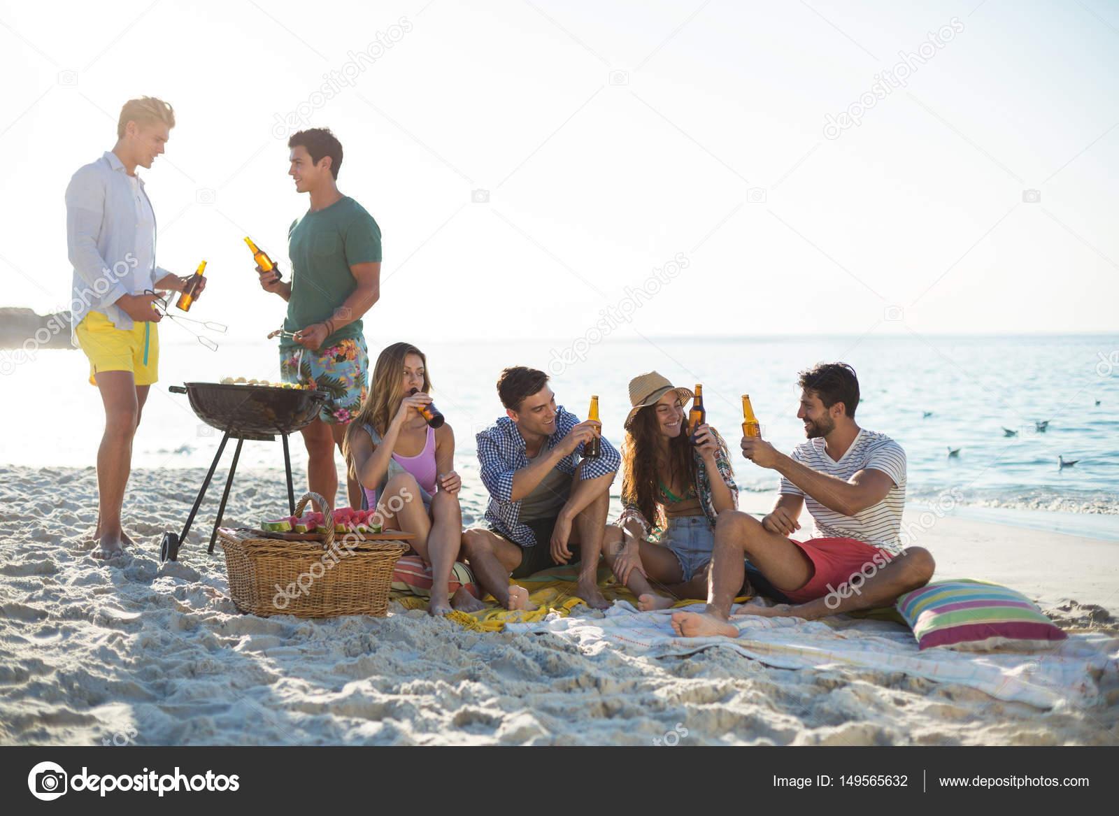 Freunde, die Getränke von Barbecue am Strand — Stockfoto ...