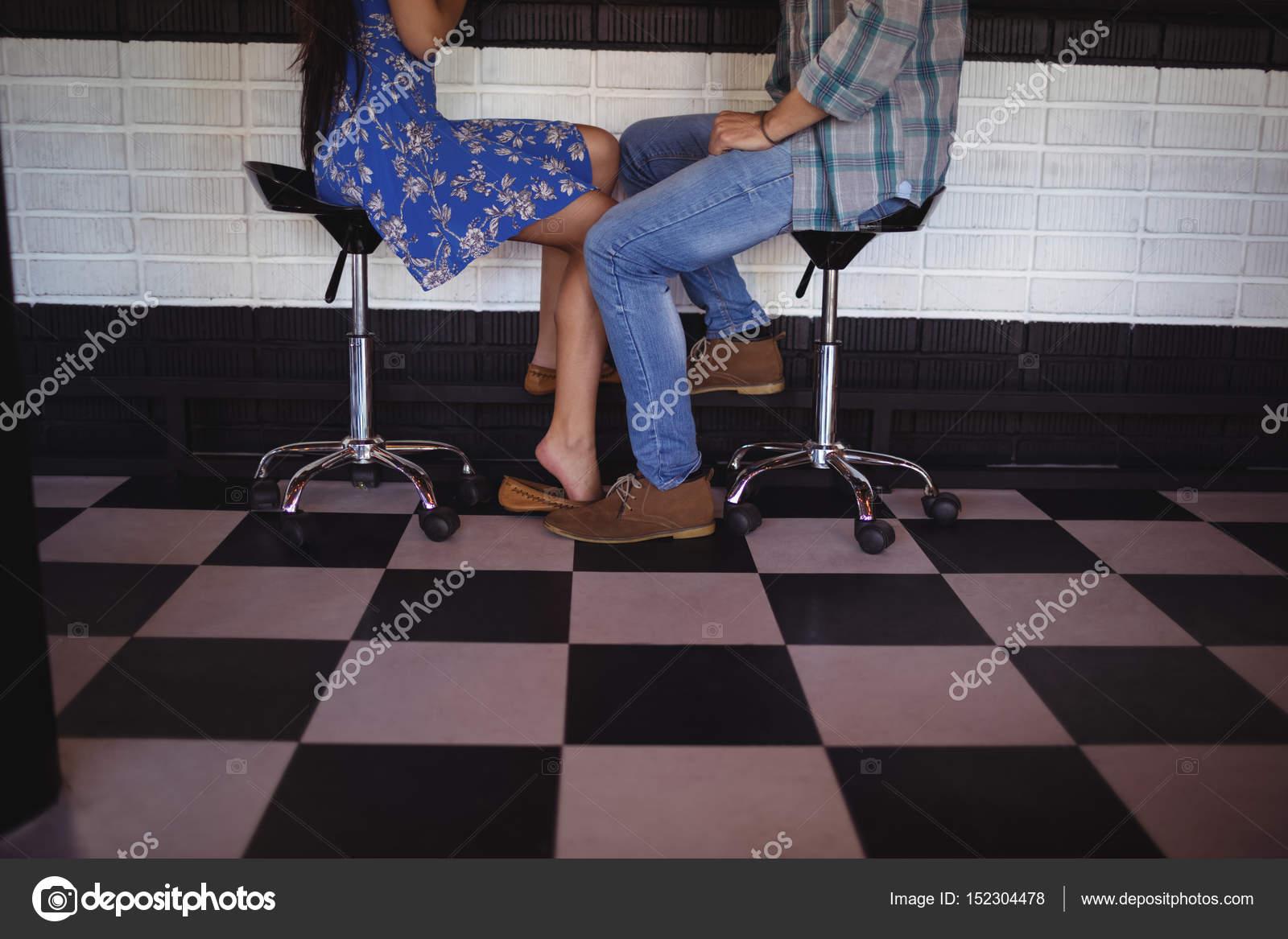 Sezione bassa della coppia che si siede su sgabelli da bar u foto
