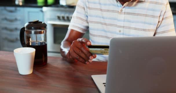 Senior man doing online shopping on laptop in kitchen at home