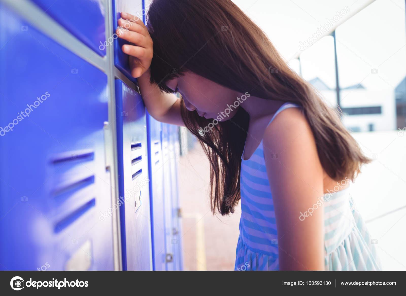 Sad girl leaning on lockers — Stock Photo