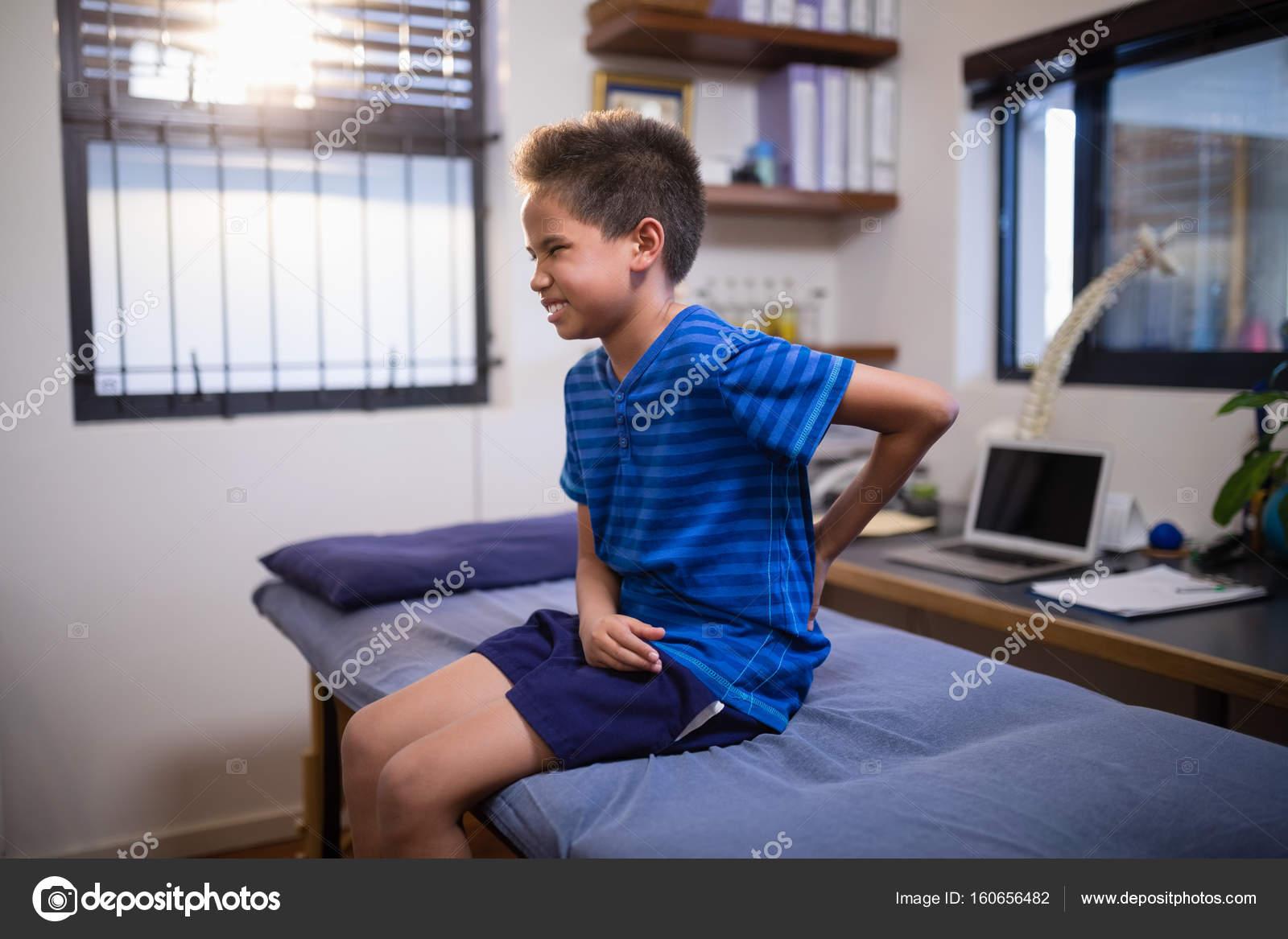 Ragazzo accigliato con mal di schiena - Foto Stock..