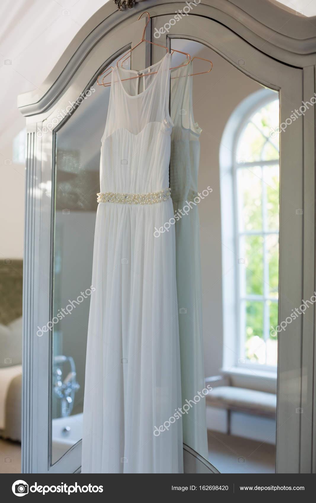 Wedding dress hanging in hanger — Stock Photo © Wavebreakmedia ...