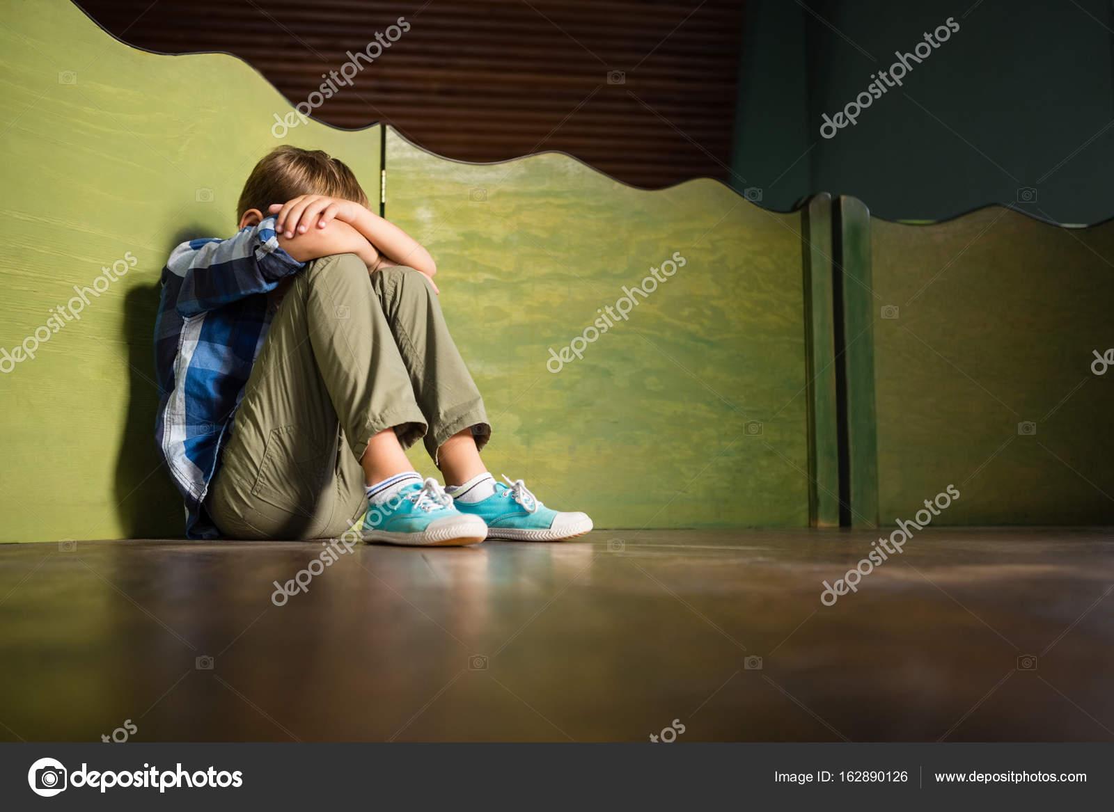 sad boy sitting with head down stock photo wavebreakmedia 162890126