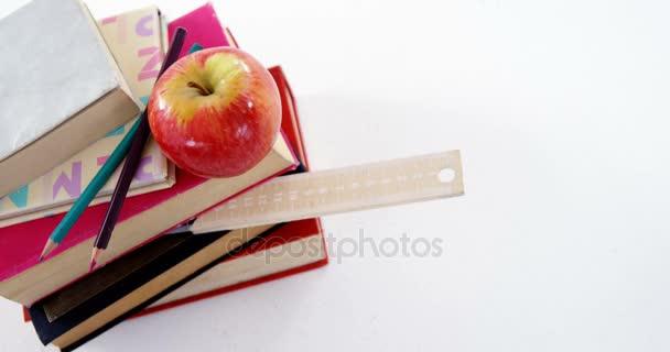 Libros, lápices de colores y manzana sobre fondo blanco — Vídeo de ...