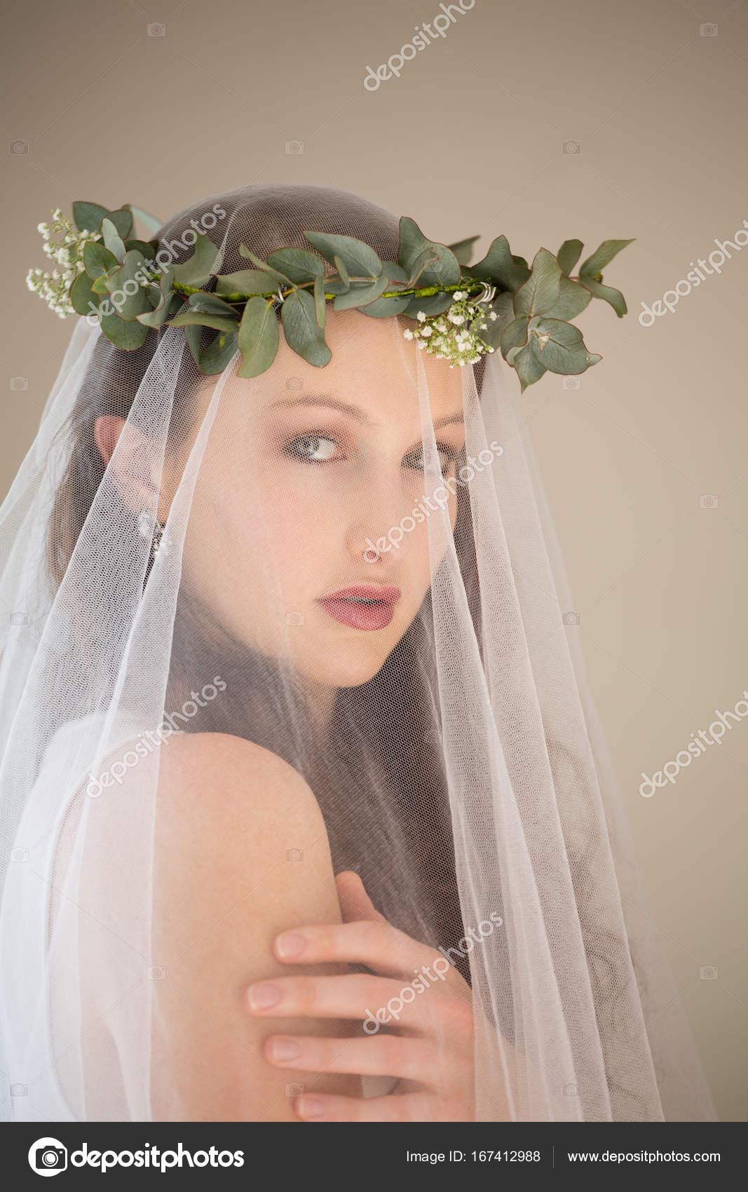 c550b021a6 Εσωτερικη πορτρέτο του όμορφη νύφη στο νυφικό και τιάρα στέκεται από τοίχο  στο σπίτι — Εικόνα από Wavebreakmedia