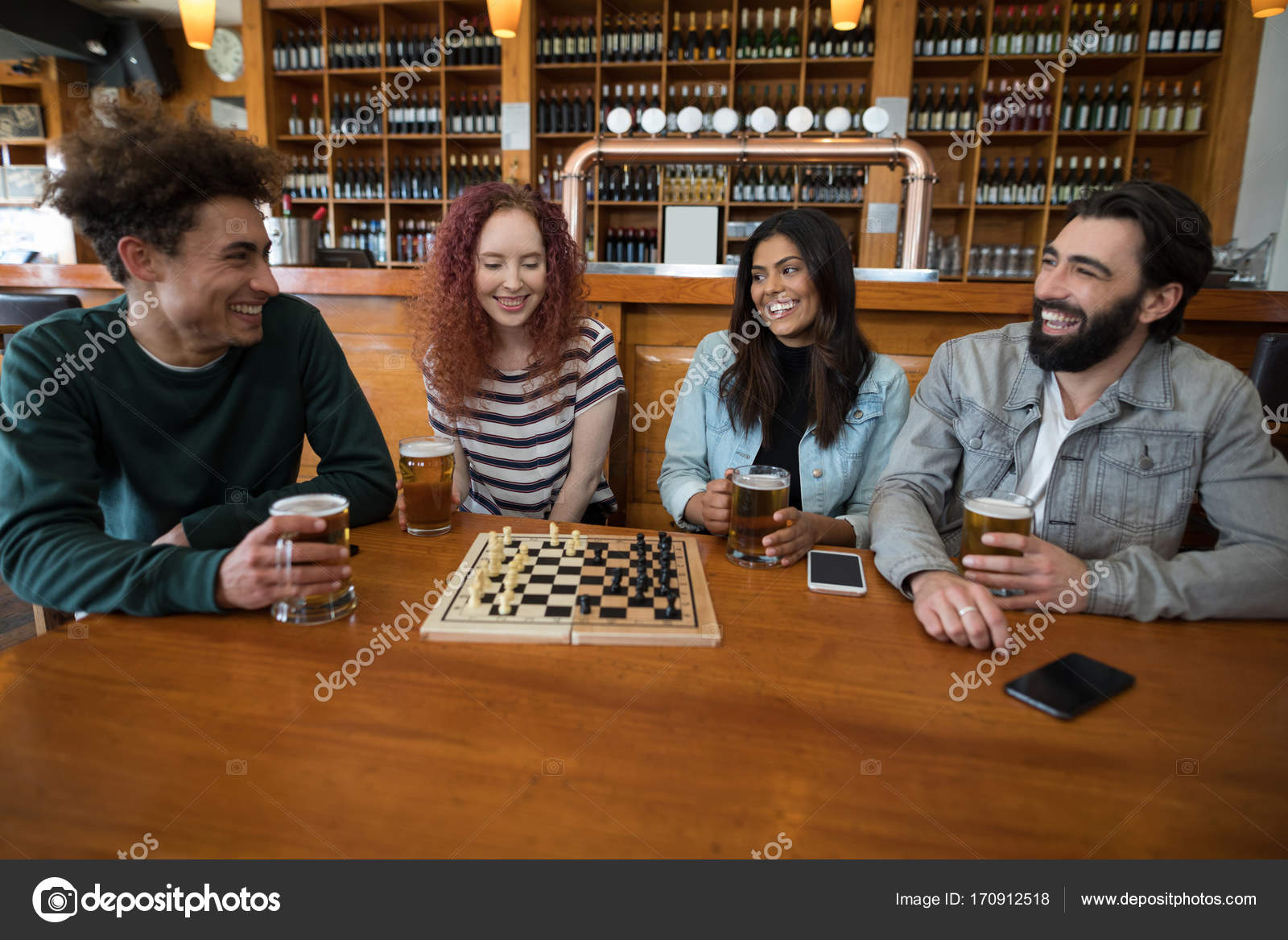 Friends playing chess while having glass of beer — Stock