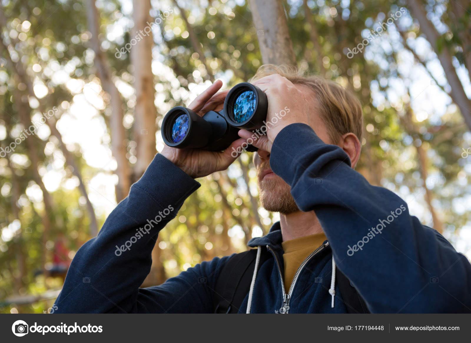 Mann wanderer die erkundung der natur durch ein fernglas