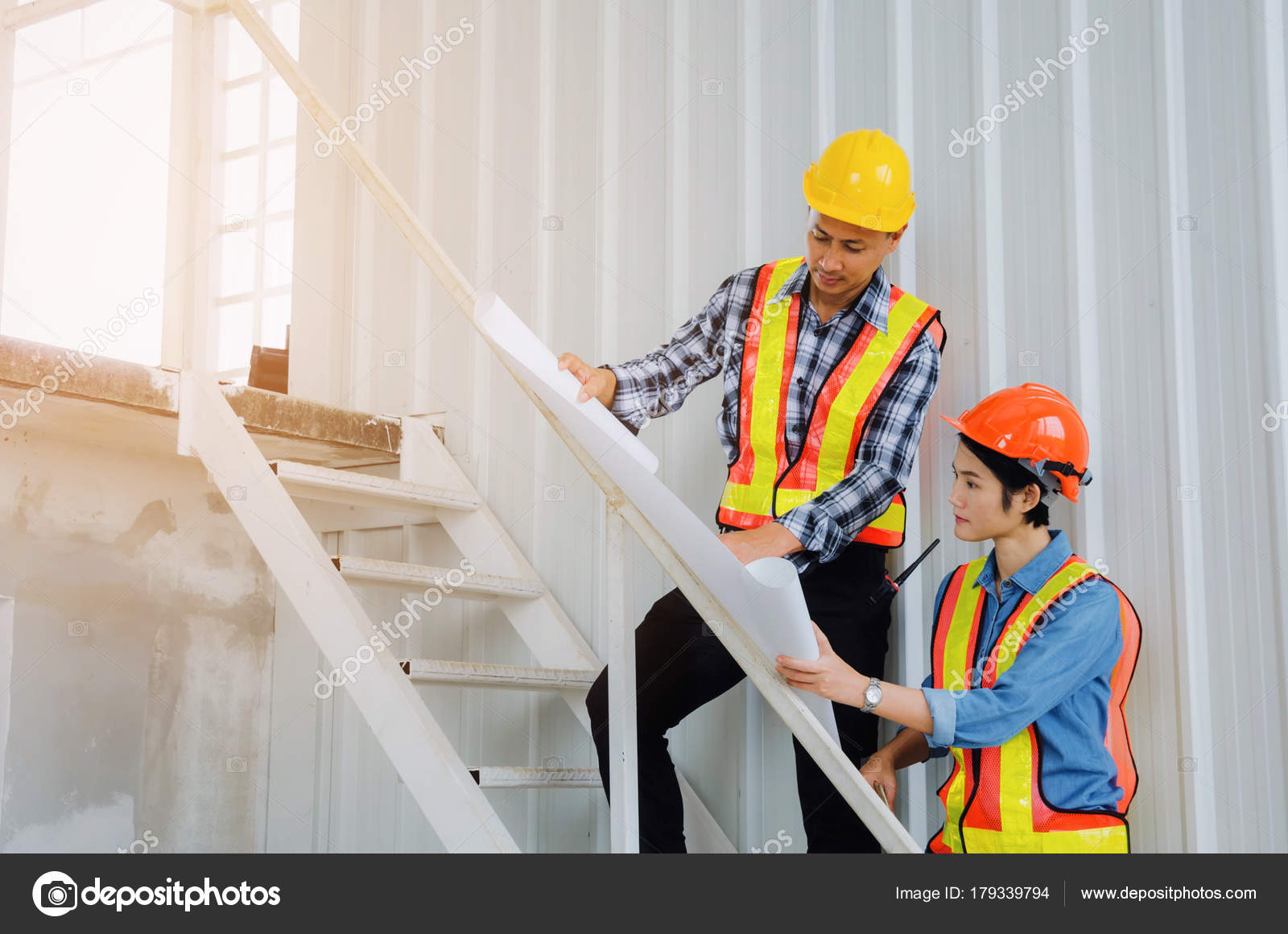 couple engineer technician man woman safety helmet looking blueprint construction stock photo
