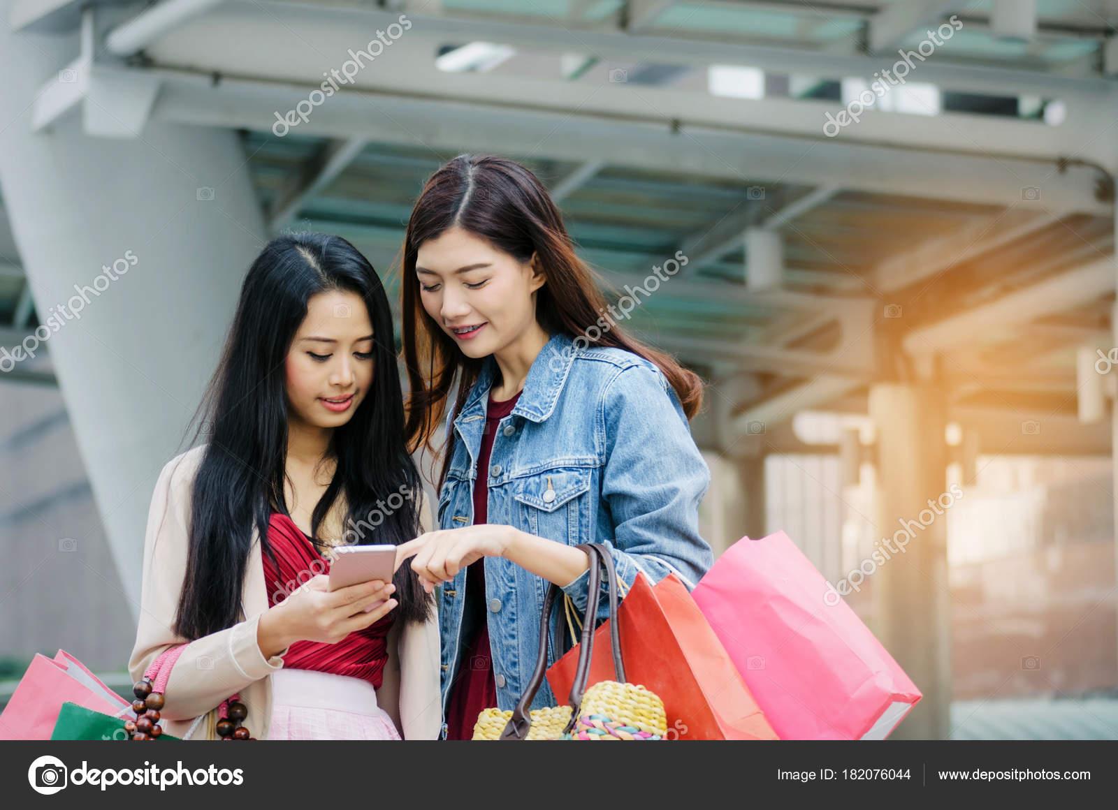 aee270cf8 Duas linda alegre jovem mulher asiática com móvel telefone inteligente segurando  sacolas andando juntos na cidade moderna