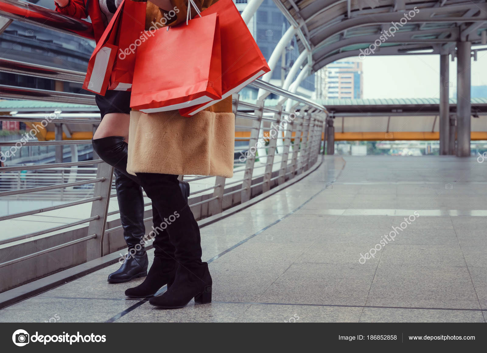 4e33b2b56 Mulher jovem e meio dois segurando muitas coloridas vermelhas sacolas  andando juntos na cidade moderna e venda verão