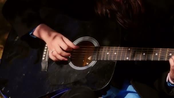 žena hrající na akustickou kytaru
